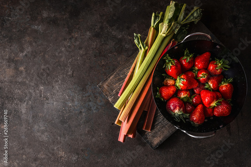 Obraz Rhubarb and strawberries on dark rustic kitchen table. Copy space. Seasonal organic food. Healthy eating and cooking - fototapety do salonu