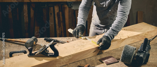 Carpenter at work on wood table with tools