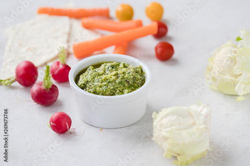 Mini vegetables served with pestos: avocado, hemp and pumpkin seeds pesto; almond, mint and basil pesto: walnut, kale and parsley pesto served with a silver spoon on light background Fototapeta