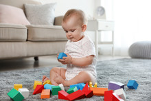Cute Baby Girl Playing With Building Blocks In Room