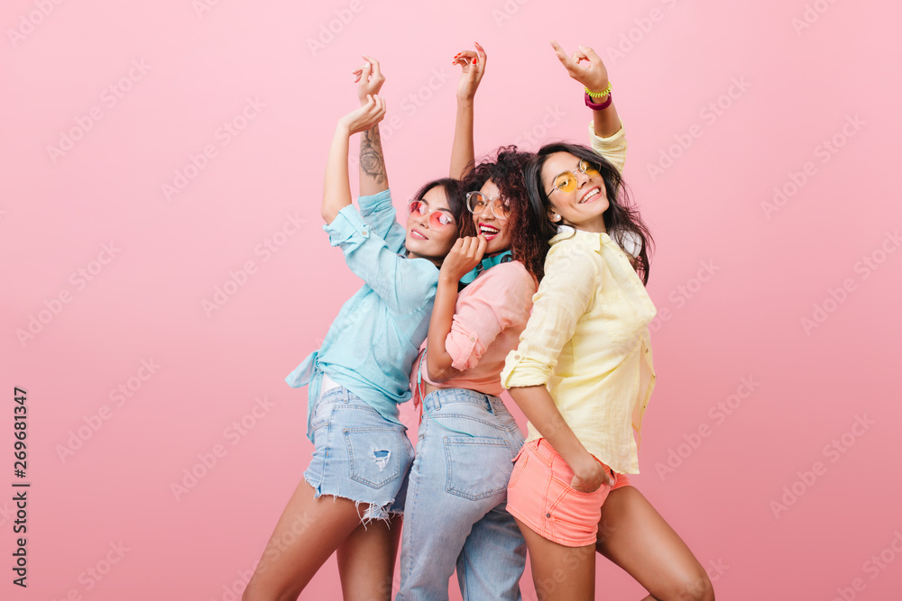Fototapety, obrazy: Glamorous hispanic woman in yellow shirt enjoying funny dance with friends. Indoor portrait of three cheerful girls chilling during photoshoot.
