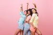 Glamorous hispanic woman in yellow shirt enjoying funny dance with friends. Indoor portrait of three cheerful girls chilling during photoshoot.