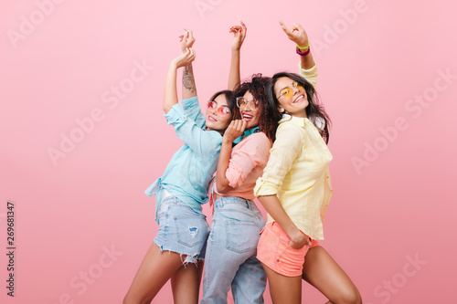 Keuken foto achterwand Dance School Glamorous hispanic woman in yellow shirt enjoying funny dance with friends. Indoor portrait of three cheerful girls chilling during photoshoot.