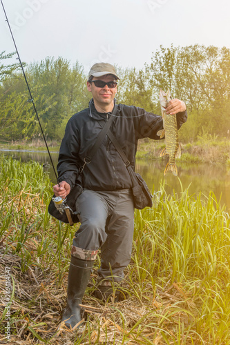 Fototapety, obrazy: Fishing. Happy fisherman holding pike fish trophy and fishing rod at river