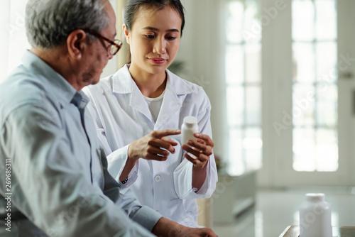 Valokuvatapetti Asian young woman explaining the bottle of pills to senior patient and explainin