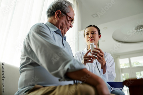 Photo  Asian young doctor holding container with pills and explaining the way of treatm
