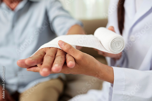 Fototapeta Close-up of female doctor putting a bandage on injured hand of senior man at hos