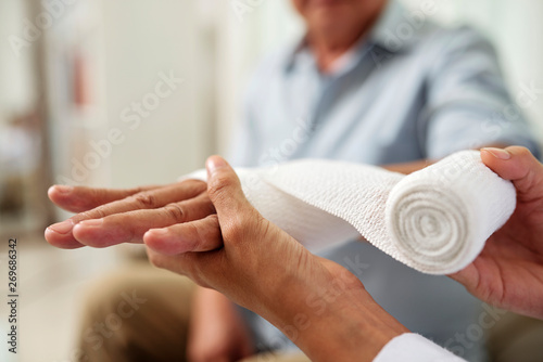 Leinwand Poster Close-up of nurse holding and bandaging hand of senior patient at hospital