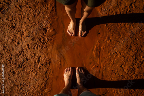 Photo Stands Magenta Feet on clay. Feet of a man and a woman on red clay, Vietnam.