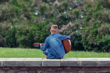 Teenager With Guitar Sitting O...