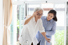 Asian Daughter Or Assistant Helping Support Senior Mother,communicates The Symptoms Of Vertigo;dizziness;migraine;sick Depressed,suffering From Headache,elderly Woman In Using Walker, Care Concept