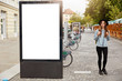Leinwanddruck Bild - Thoughtful female tourist strolls on footway near lightbox with mock up blank space for your advertising content or commercial information. Street style concept. Focus on billboard at sidewalk