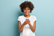 Half length shot of Afro woman holds mobile phone, enjoys nice talk online in social networks, reads funny article in internet, uses cellular, wears white t shirt and spectacles, isolated on blue wall