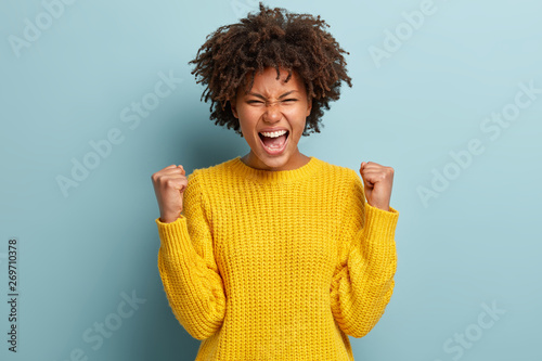 Fotografiet  Successful dark skinned female student happy to get scholarship, clenches fists, accomplishes goal, exclaims finally victory, stands amused over blue background