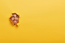 Glad Caucasian Man With Toothy Smile, Has Bristle, Looks Positively Aside, Shows Face In Paper Hole, Isolated Over Yellow Background With Blank Space. Positive Emotions. Man Peeks Through Ripped Paper