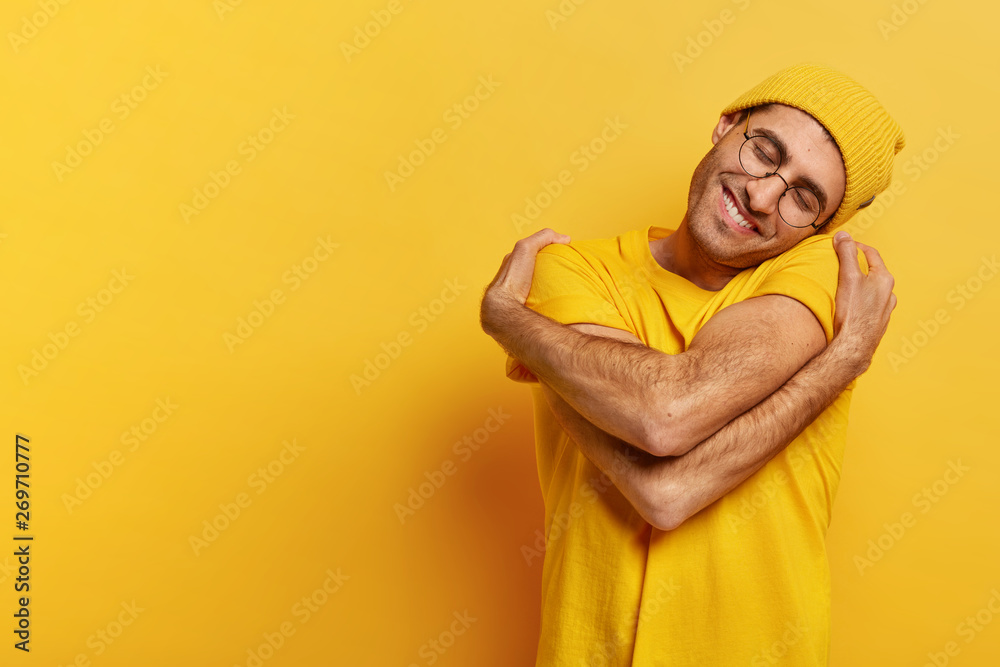 Fototapeta Pleased Caucasian man hugs himself, has high self esteem, tilts head, has toothy smile, wears casual yellow hat and t shirt, stands indoor, copy space for your promotional content, feels comfort