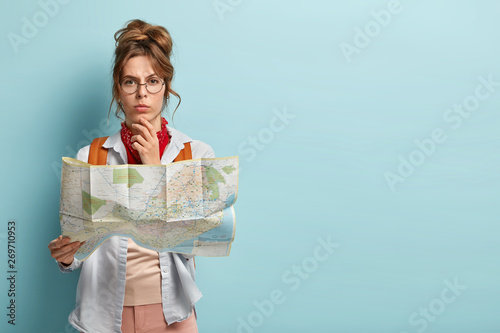 Studio shot of serious thoughtful female tourist holds chin, plans her trip, hol Canvas