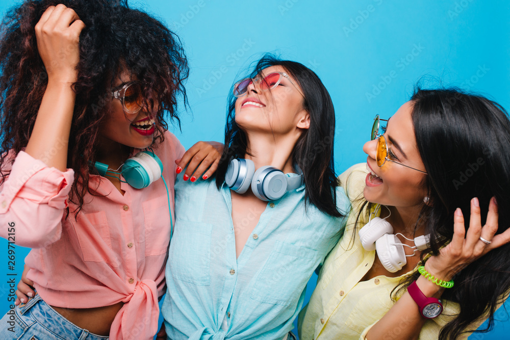 Fototapety, obrazy: Spectacular latin girl laughing, standing between international female friends. Indoor portrait of blissful ladies in casual attires joking in studio.