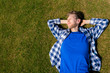 young man relax chill outdoor on the green grass lawn under the summer sunshines