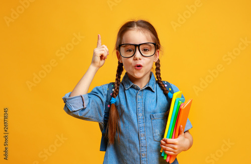 Photo sur Toile Les Textures funny child school girl girl on yellow background .