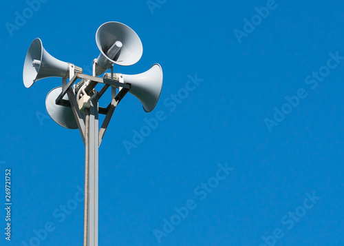Four loudspeakers attached to a rack on a blue background. Canvas Print