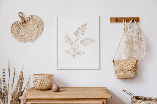 Carta da parati  Stylish korean interior of living room with brown mock up poster frame, elegant accessories, flowers in vase, wooden shelf and hanging rattan leaf, bags