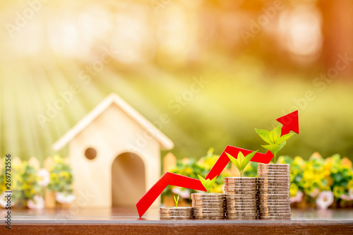 Fotografía  Stack gold coin with plant on the top and red arrow graph with growing value and wooden house put on the table in the public park, Business investment or loan for real estate concept