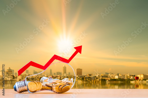 Coin in the bottle of light bulb and arrow graph with growing value money put on the wood on photo blur cityscape on sunlight background, Business investment and saving energy concept Canvas-taulu