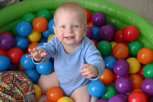 One Year Old Baby Boy Is Playing In Ball Pool On Safety Playground. Having Fun With  Toys