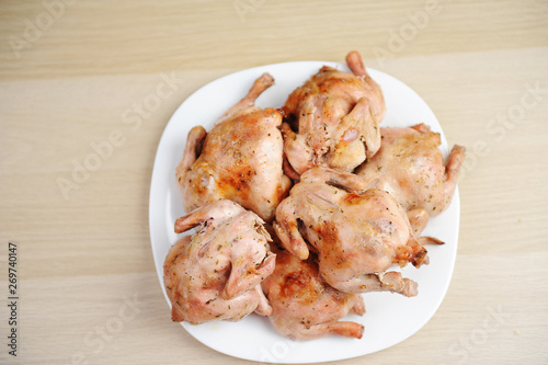 Six baked cornish hens on white plate top view Canvas Print