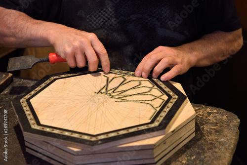 Fotografija  Craftsman working on handmade inlaid platter in a Alhambra shop Granada