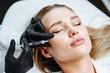 Leinwandbild Motiv Young woman receiving plastic surgery injection on her face