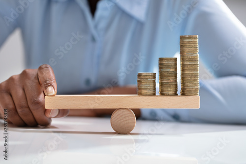 Obraz Businesswoman Balancing Stacked Coins With Finger - fototapety do salonu