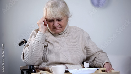 Photo Unhappy old female in wheelchair refusing to eat hospital lunch, feeling lonely