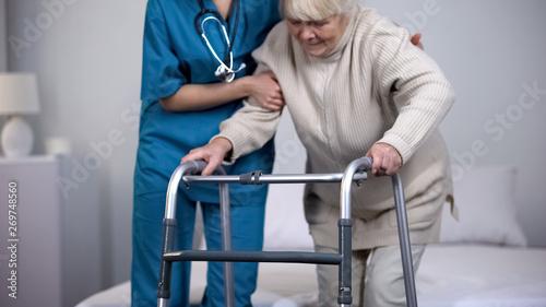 Fototapeta Nurse assisting patient walking frame, hip joint replacement rehabilitation obraz