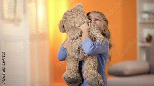 Fototapeta Cute little girl hugging teddy bear, favorite toy, happy childhood, best present obraz na płótnie