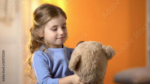Fototapeta Preschool girl looking at teddy bear, playing with toy, happy little princess obraz na płótnie