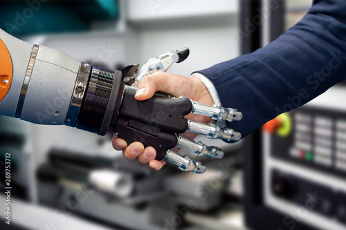 Poster Echelle de hauteur Hand of a businessman shaking hands with a Android robot.