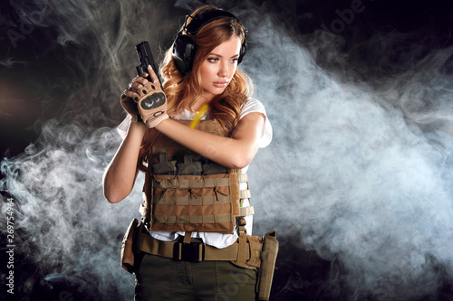 Photo  Woman in protective armour and headphones holds gun in hands, posing over dark smoky background