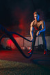 canvas print picture Determined shirtless male athlete performing waves by battle rope, keeping fit in cross fit club.