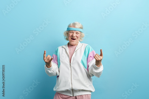 Obraz Cute hipster grandmother smiling and making rock sign against blue studio background - fototapety do salonu