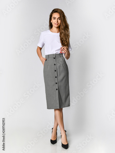 Cuadros en Lienzo Young beautiful woman posing in new white bluesque and gray skirt on high heels