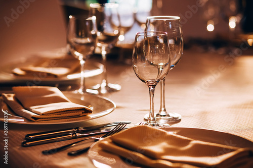 served table with white tablecloth. white plates, wine glass, fork, knife - 269763336