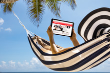 Woman Watching News On Digital Tablet Against Blue Sky