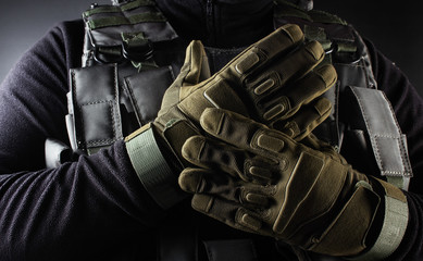 Warrior soldier in tactical gloves standing front view closeup.