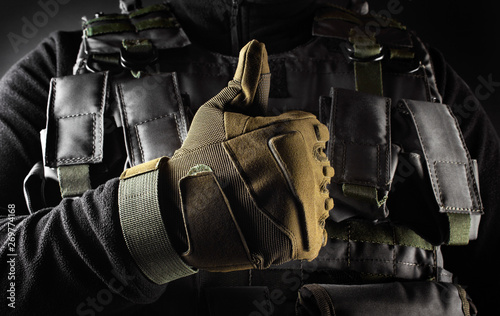 Cuadros en Lienzo Soldier in tactical gloves showing like front view closeup.