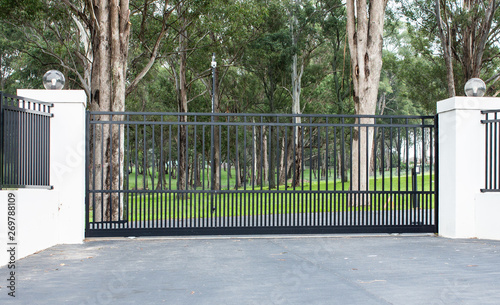 Fotografía Metal driveway rural property entrance gates set in brick fence with lights and