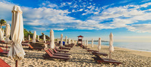 Sun Loungers And Umbrellas On An Empty Sandy Beach. Summer Sunny Cloudy Blue Sky. Cam Ranh. Vietnam.
