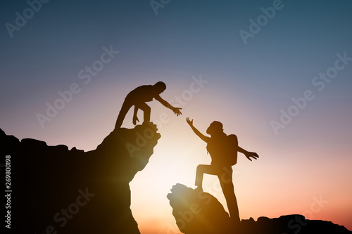 help and improve concept, silhouette people helping other hiker climbing rock an Canvas