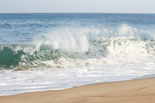 Backspray Cresting Wave With Backwash Foam Breaking On A Sandy Shoreline